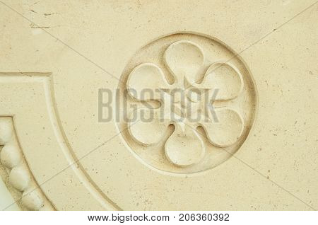 Old plaster bas-relief in the form of a flower in a round frame with a small piece of pattern