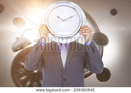 Businessman holding wall clock in front of face against digital image of alarm and wall clocks