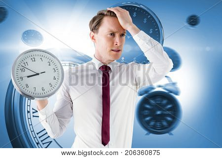 Anxious businessman holding a clock  against computer generated image of clocks