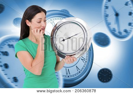 Brunette looking at wall clock against graphic image of wall clocks