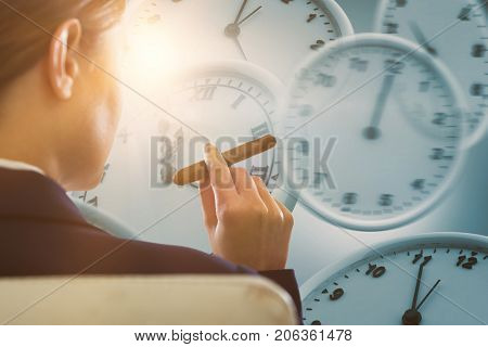 Businesswoman holding cigar against computer generated image of wall clocks