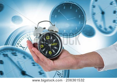 Cropped hand of male executive holding alarm clock against digitally generated image of wall clocks