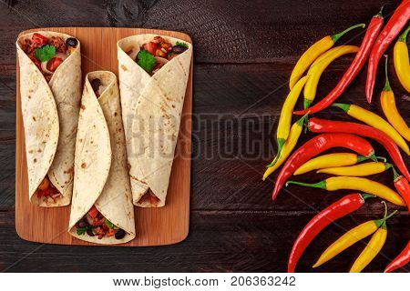 An overhead photo of Mexican burritos with beef, rice, black beans, and vegetables, with  chili peppers, and a place for text, shot from above on dark wooden rustic textures