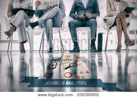 business analytics graphic against group of well dressed business people waiting
