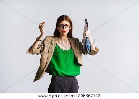 red-haired girl with glasses holds a pointer and folder in her hands and is indignant