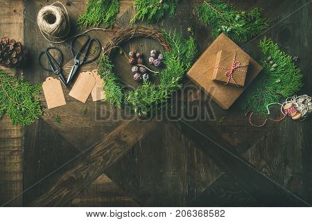 Preparing for Christmas or New Year holiday. Flatlay of fur tree branches, gift boxes, wreaths, rope, pine cone, scissorsand stickers over rustic wooden table bbackground, top view, copy space