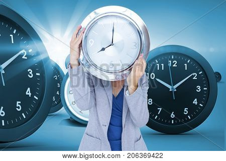 Businesswoman holding clock in front of face against digital composite image of clocks
