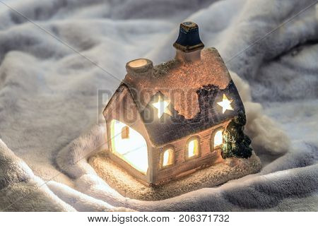 Сhristmas fairytale candlestick house with with brightly burning candle. Christmas decoration.