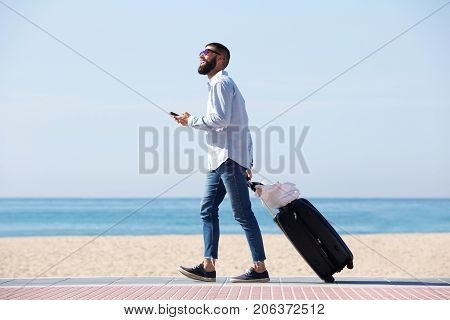 Full Length Happy Traveler Walking By Sea With Luggage And Cellphone