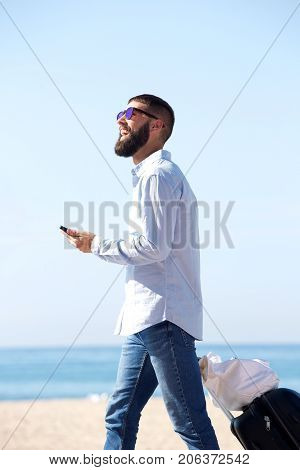 Side Of Happy Traveler Walking On Beach With Luggage And Mobile Phone