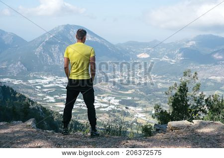 The man stand a hill and looks at the unleashed landscape. Seascape with a bird's-eye view.
