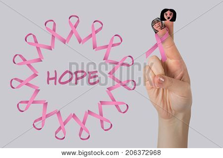 Cropped image of hand with pink breast cancer awareness ribbon against light grey