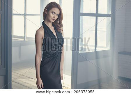 Beautiful sexy young woman. Portrait of girl in long black dress, mystical, mysterious style, smoke lighting background