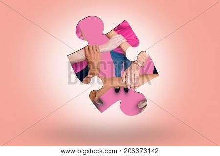 Women in pink outfits joining in a circle for breast cancer awareness against salmon background