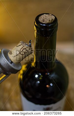 A dark bottle of wine with a jammed cork and a bottle opener with a damaged cork on a light brown background in warm light.