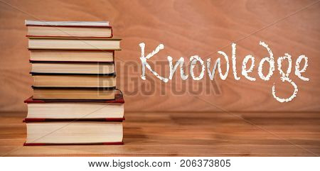 Knowledge text against white background against hardcover books stack