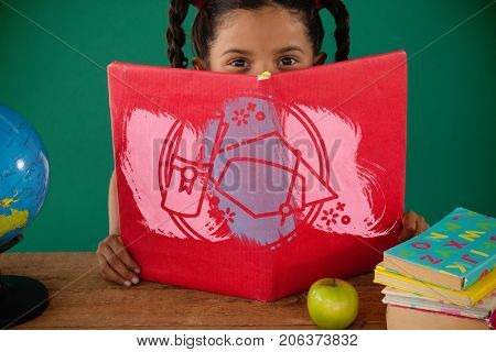Illustration of mortarboard and degree against schoolgirl hiding behind a book against green background