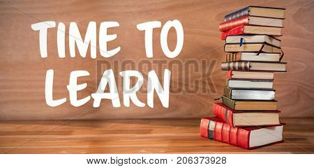 Time to learn text against white background against stack of various books on table
