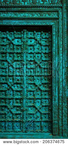 Antique, weathered, intricately carved wooden door painted in grunge blue color. Partial view of an old wooden door frame and panel.