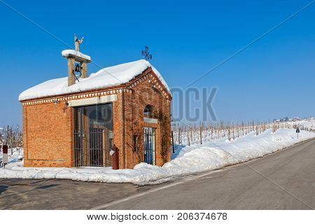 Small chapel on the roadside and vineyards covered with snow under blue sky in Piedmont, Northern Italy.
