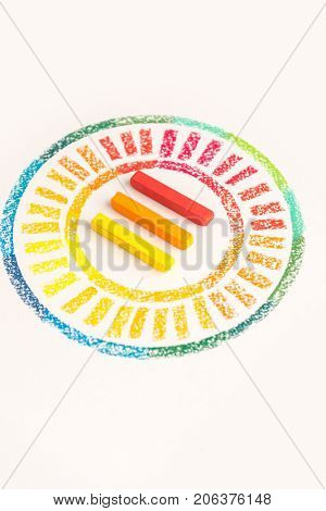 Close up photo of circle drawn with colorful pastel chalks with three chalks in the middle, over white background