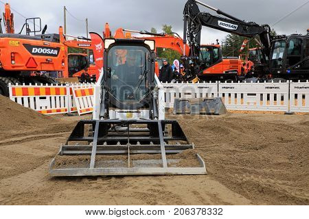 HYVINKAA FINLAND - SEPTEMBER 8 2017: Operator levels ground with Bobcat T450 Compact Track Loader and landplane attachment on sand work site on Maxpo 2017.