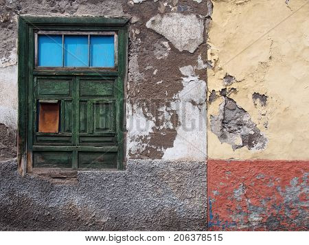 detail of empty derelict small house with decaying bricks broken plaster and green window with fading colors