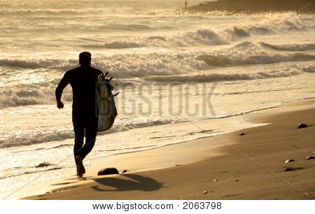 Surfer Running At Sunset