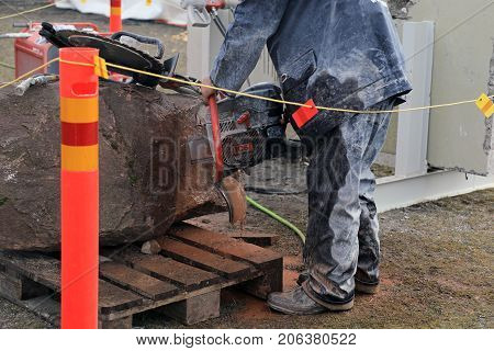 HYVINKAA FINLAND - SEPTEMBER 8 2017: Man is sawing natural granite stone with ICS Chain Saw on Maxpo 2017.