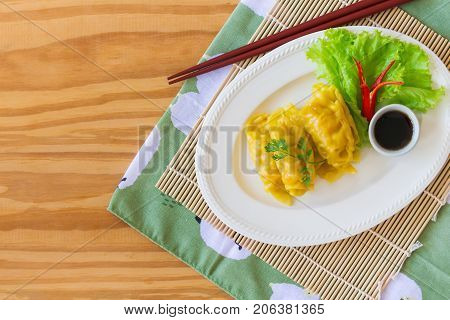 Homemade minced pork dumpling with dipping soy sauce on wood table in top view flat lay with copy space. Delicious dumpling or dim sum for breakfast or dinner. Dim sum or dumpling is Chinese food. Dim sum ready to served, flat lay style.