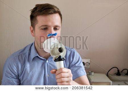 Young man testing breathing function by spirometry. Take care about health.