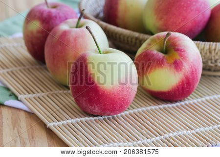 Stack of fuji apple on bamboo mat and in basket put on wood table for background or wallpaper.Delicious sweet and juicy fuji apple suitable for salad cooking or bakery.Fuji apple has origins in Japan. Prepare apple for cooking or bakery.
