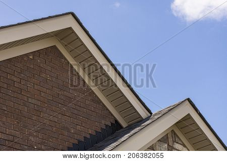 Roof Showing Soffit On The Front Of A Brick And Stone House.
