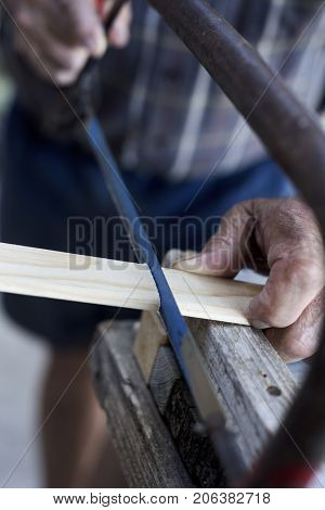 closeup of an old caucasian man sawing a wood strip with a hand saw