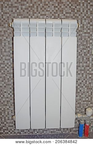 Heating white radiator on a background of brown mosaic tiles