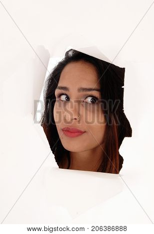 A gorgeous face of a young woman with brunette hair looking trough a hole in a paper isolated for white background