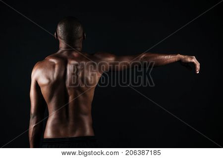 Back view photo of half-naked muscular sports man, with right hand up, isolated on black background