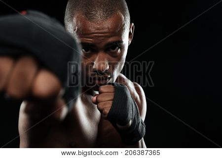Close-up photo of afroamerican boxer, showing his fists, over black background