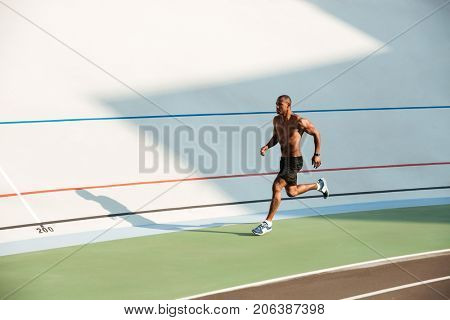 Full length portrait of a muscular half naked sportsman running on a track field outdoors