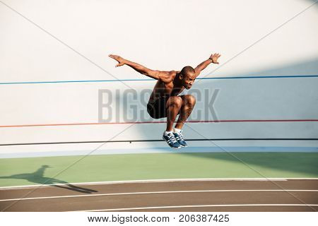 Full length portrait of a half naked strong fit african sportsman jumping at the track field outdoors