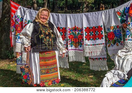 TIMISOARA ROMANIA - SEPTEMBER 23 2017: Old romanian woman who sells traditional products at a fair called Fair of craftsmen organized by the City Hall Timisoara.