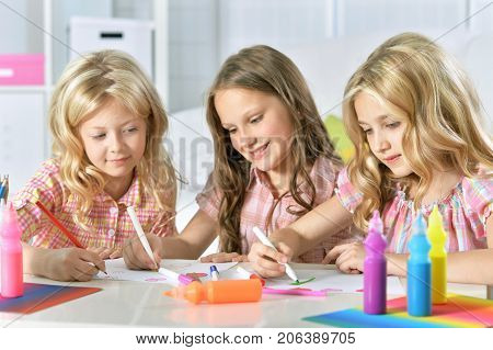 three cute girls sitting at table and drawing with pencils