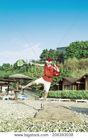 New Year On The Beach. Santa Claus Walking With A Bag Of Gifts On The Beach. The Concept Of A Holida