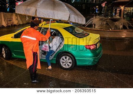 BANGKOK THAILAND - July 24: An unidentified Security guard in rain holds an umbrella for an unidentified woman while she gets into a taxi on July 24 2017 in Bangkok.