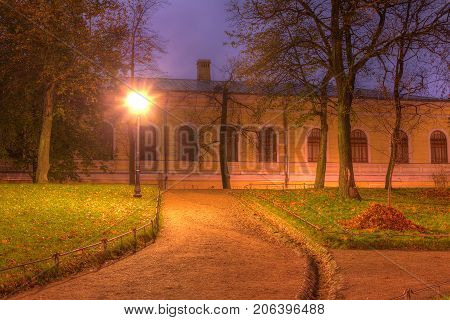 Dusk autumn view of park footpath and building of State University of Communication in Yusupov Garden Saint Petersburg Russia