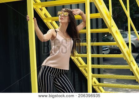 A beautiful girl with sunglasses in a beige T-shirt and black breeches in a white stripe. Against the background of a black container with a yellow staircase. Artistic photography. beauty and fashion style.
