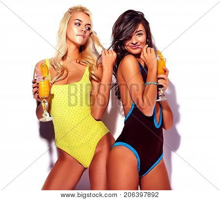 Two trendy hipster girls blonde and brunette models drink cocktails in colorful swimwear on white background poster