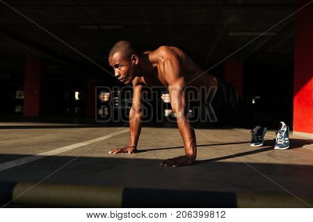 Portrait of a half naked muscular afro american sportsman doing plank exercises indoors