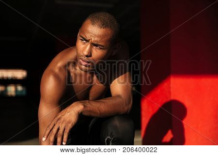 Close up portrait of a muscular half naked african sportsman sitting on his knee and looking away indoors