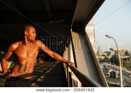 Portrait of a exhausted sweaty half naked african sportsman resting while leaning on a handrail indoors